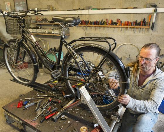 Réparation d'un vélo par un compagnon emmaus